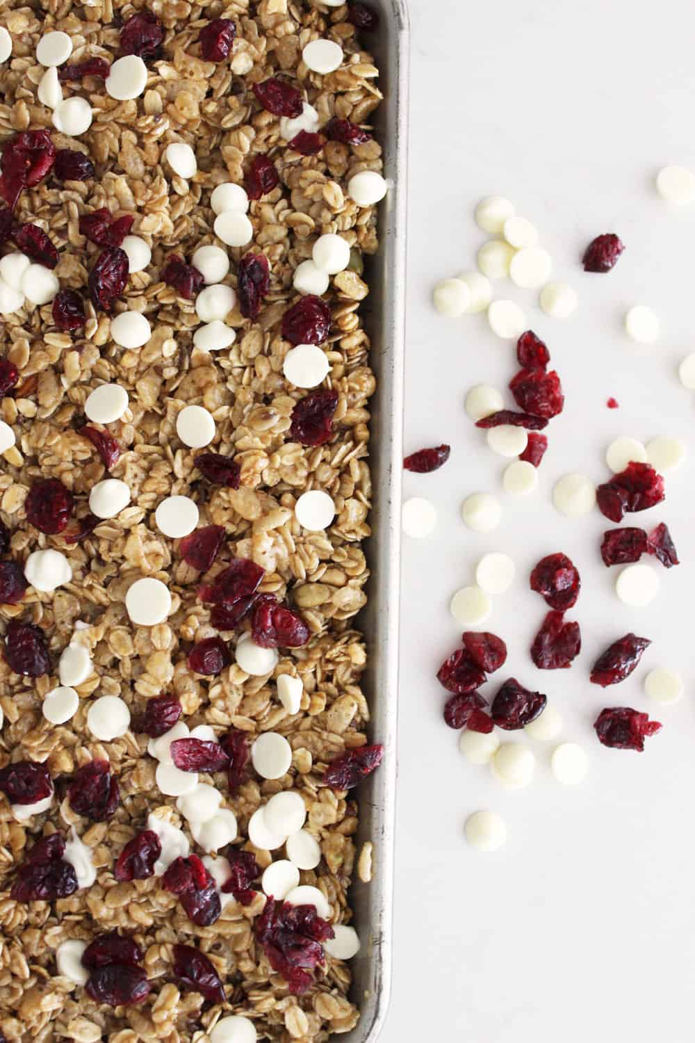 White chocolate cranberry granola bars pressed in a pan ready to cut