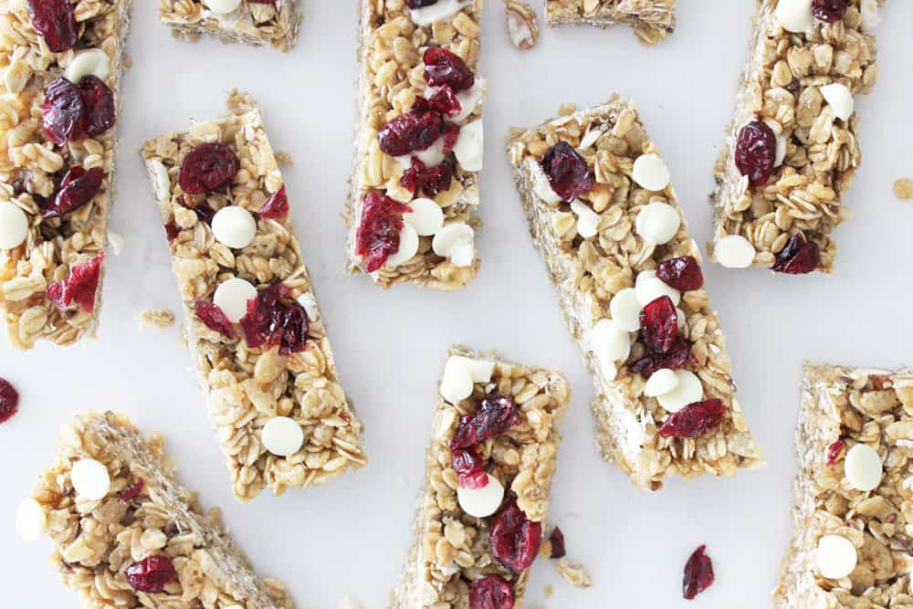 homemade granola bars with cranberries and white chocolate chips on a white countertop