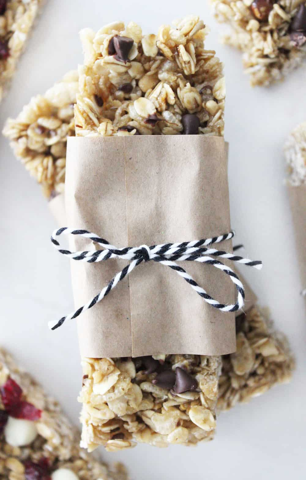 homemade chocolate chip granola bars stacked on top of each other wrapped in paper
