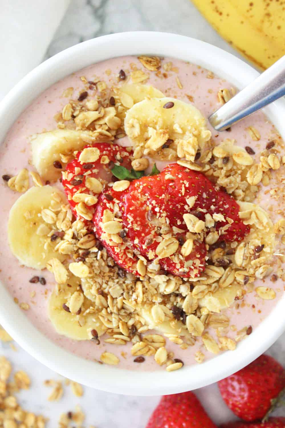 strawberry smoothie bowl topped with granola and fresh fruit with a spoon ready to eat.