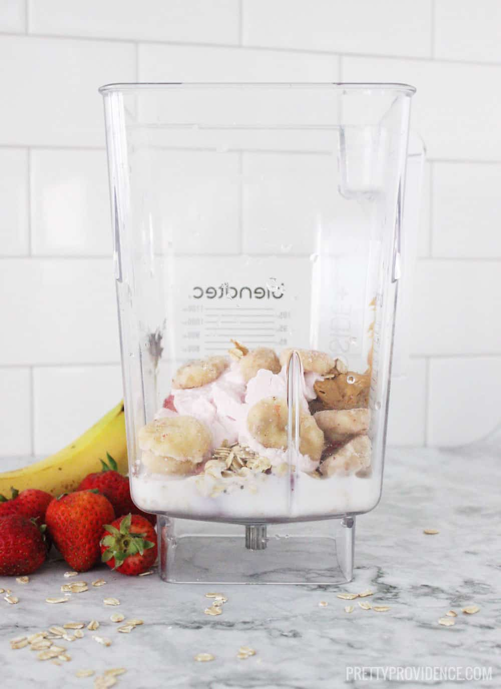 smoothie ingredients in blendtec on granite counter next to strawberries