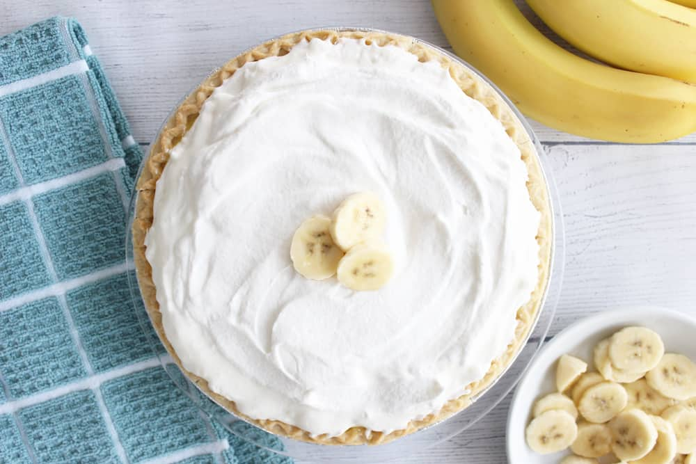 a full banana cream pie next to a blue towel, 3 bananas and some sliced banana on a white plate