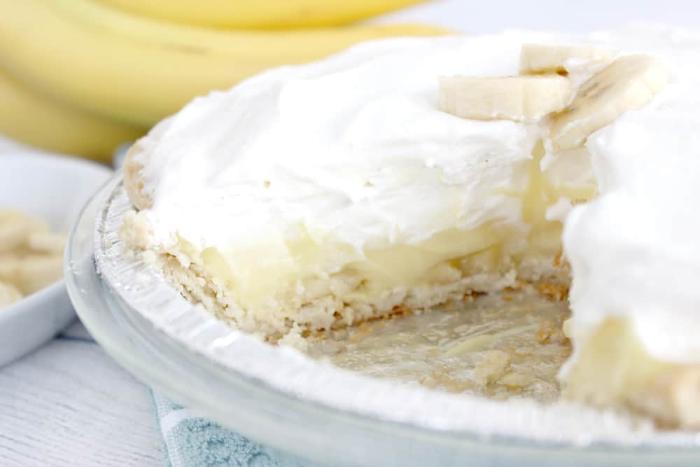 banana cream pie with a slice missing. bananas in the background