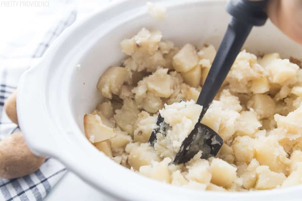 Potato masher in mashed potatoes in a slow cooker bowl.