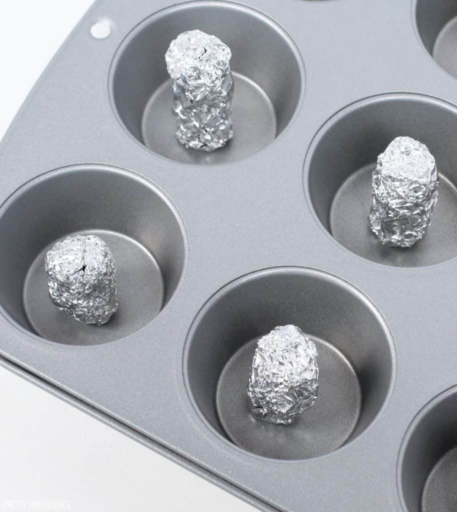 Tin foil cylinders in muffin pan to make donuts without a donut pan.