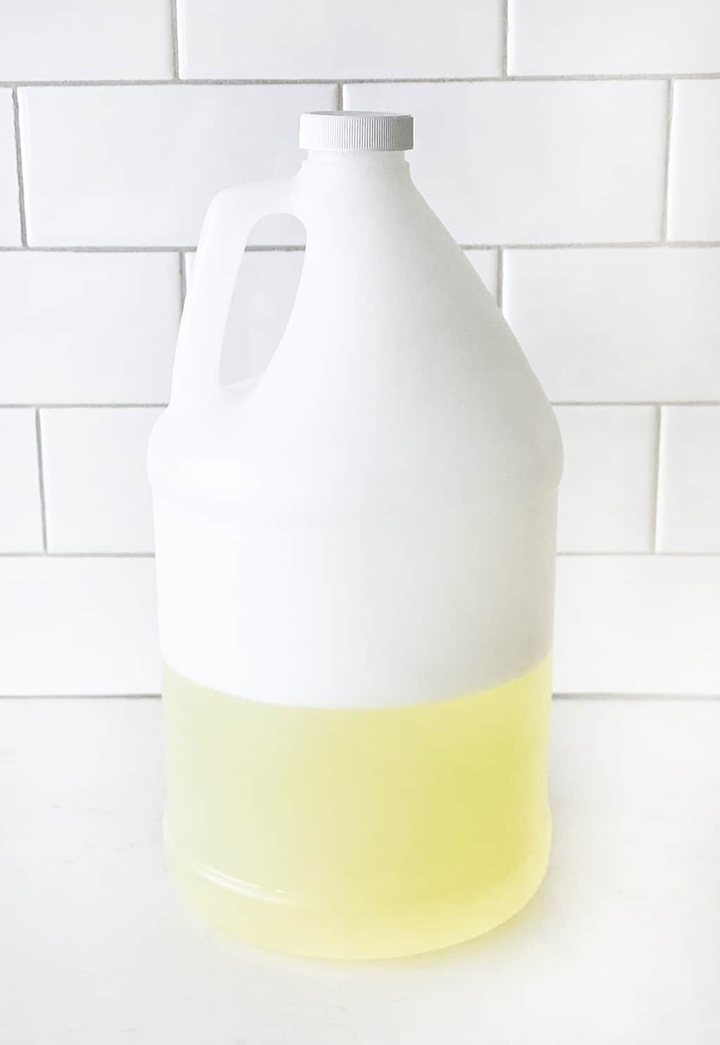 a white gallon jug full of homemade bubbles on a white counter