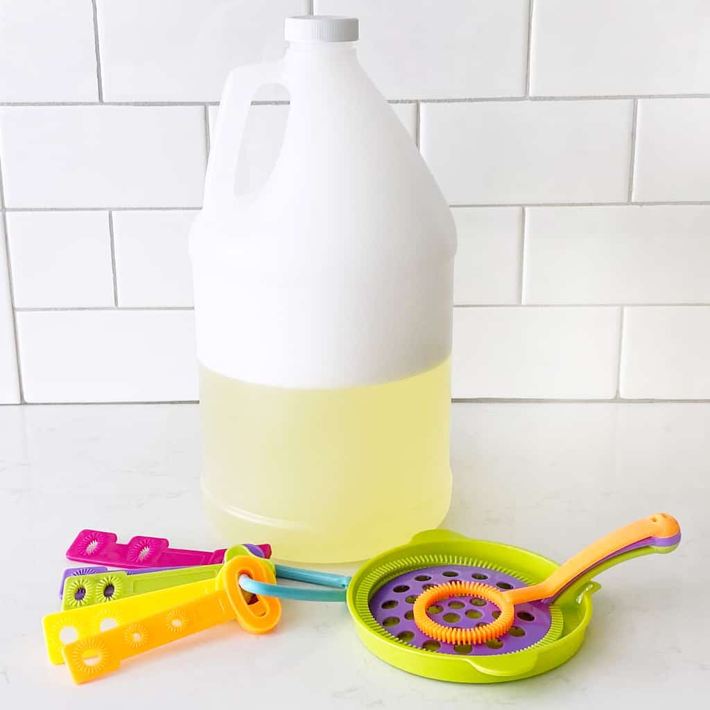 bubble solution in a white gallon jug by some bubble wands