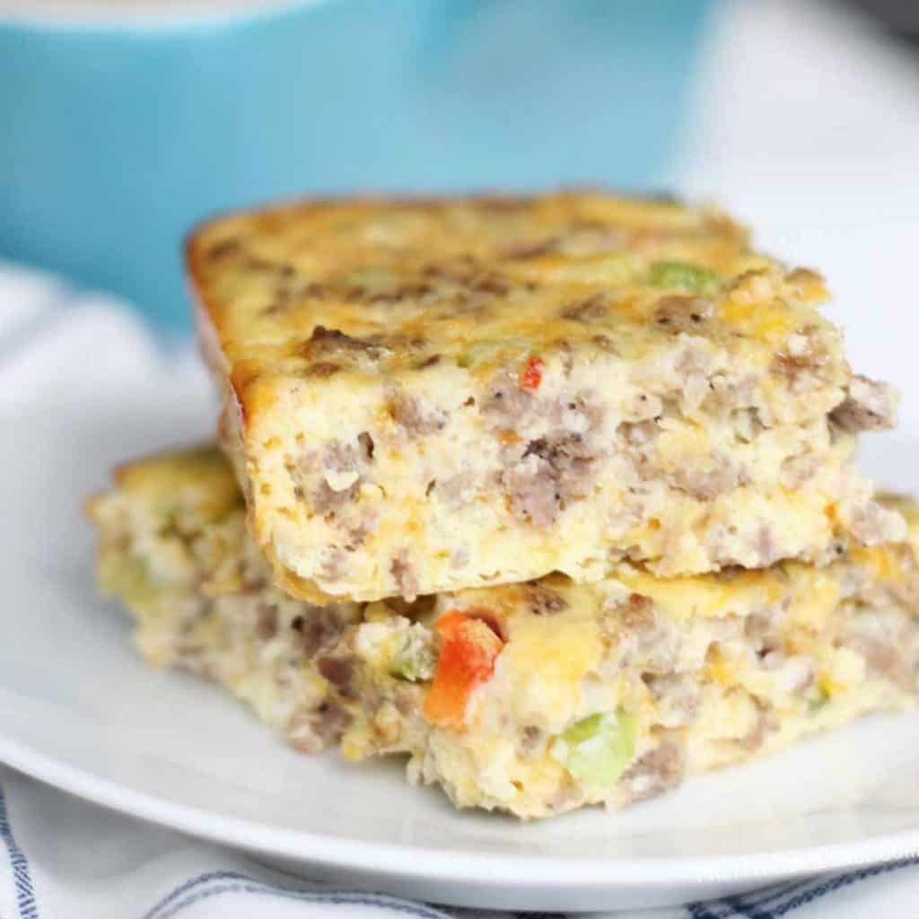 Breakfast casserole with sausage, eggs, cheese and bell peppers on a white plate