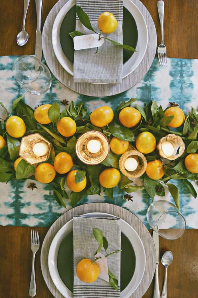 Thanksgiving table setting. Shibori table runner blue and white, with orange citrus fruit and leaves, and black plates with gray napkins.