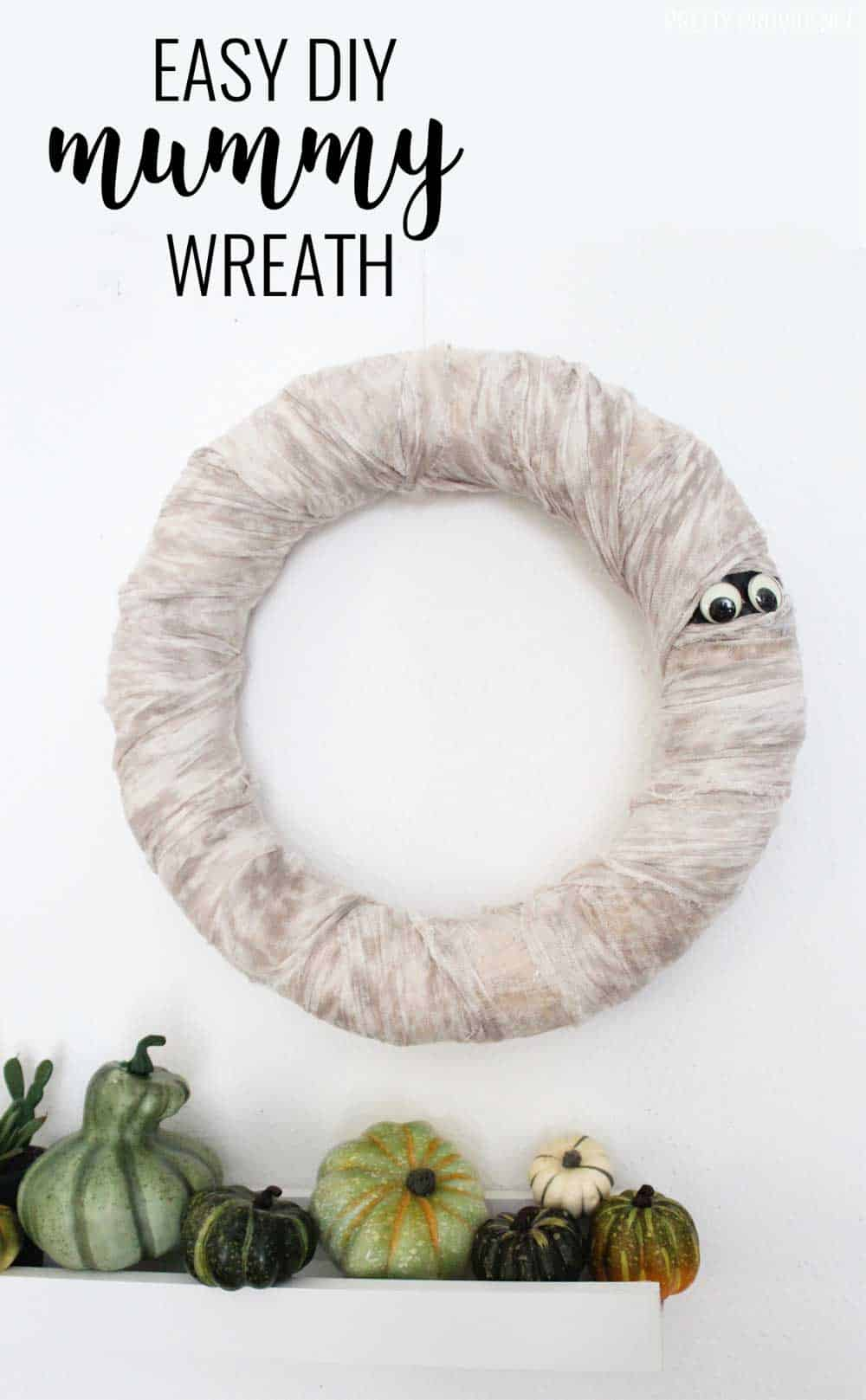 Halloween Wreath that looks like a mummy - wreath wrapped in cheese cloth with googly eyes peeking out.