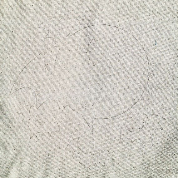 Traced Picture of Bats and a moon onto a Tote Bag with pencil.