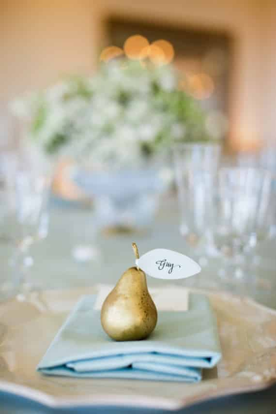 Thanksgiving place setting: gold pear on a blue napkin. A white leaf bearing someone's name in calligraphy on the pear.