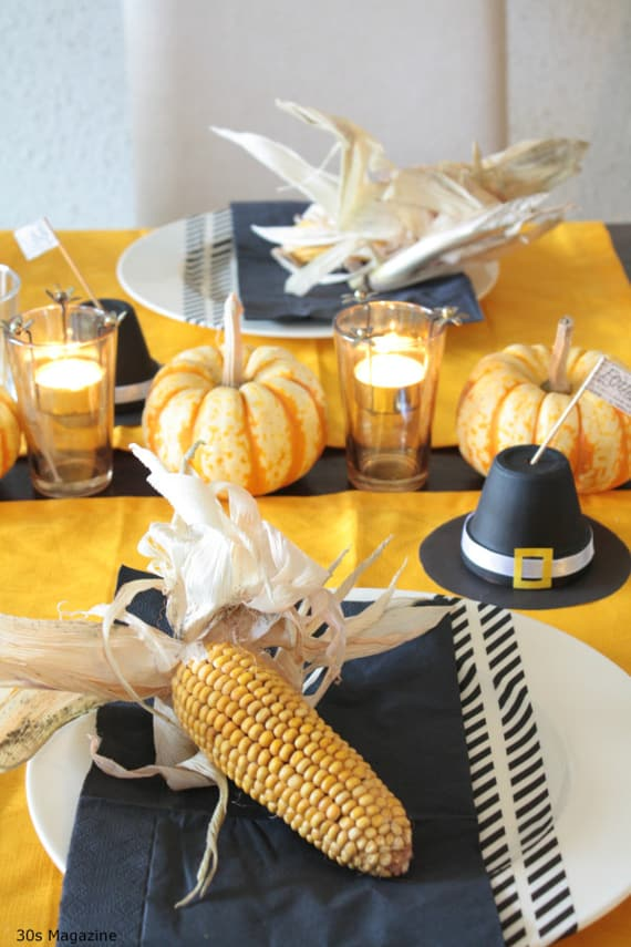 Thanksgiving table: pilgrim's hat place card holders, orange pumpkins and black napkins with corn and husks on the plates.