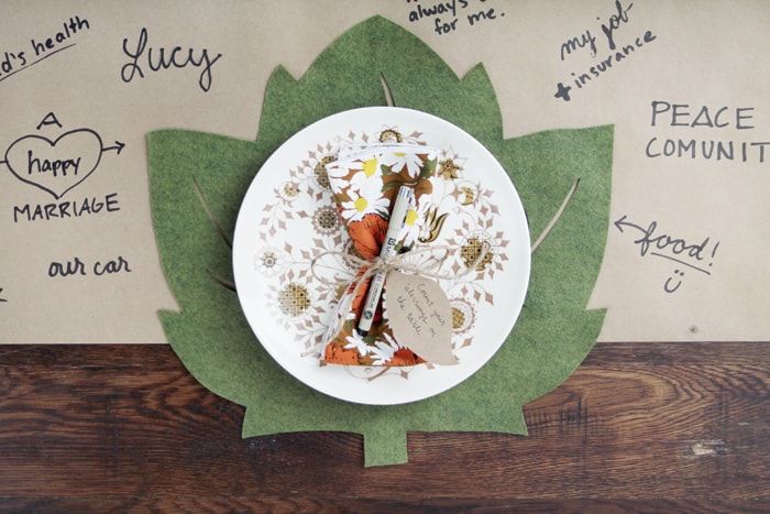 Green Felt Leaf Thanksgiving Place Mat on a kraft paper table cloth and under a plate.