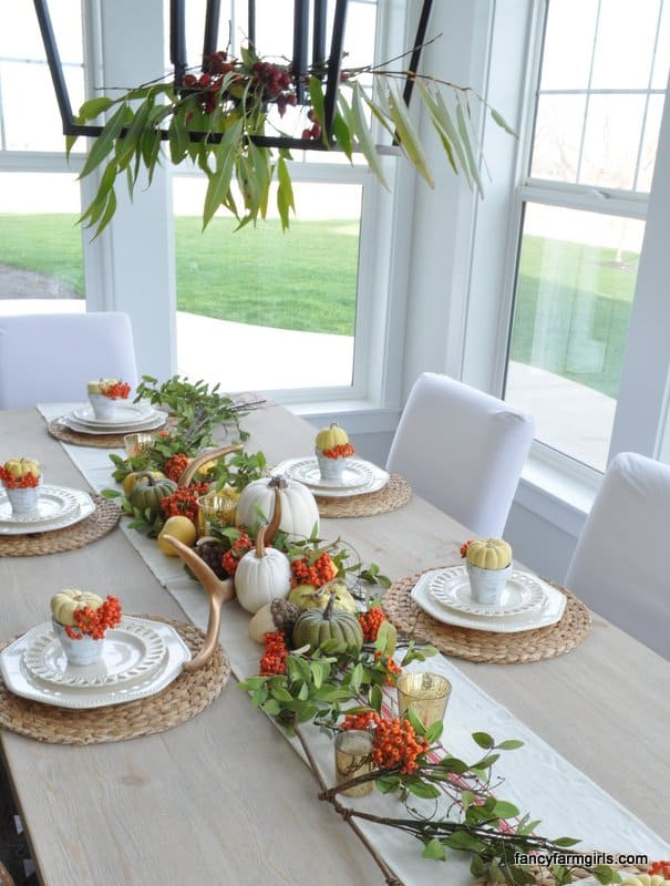Thanksgiving Tablescape Orange, white, green pumpkins, greenery and berries on a burlap table runner.