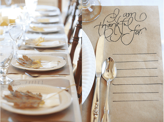Thanksgiving table setting, with gold leaves on white plates, simple and pretty paper placemat that says 'I am Thankful for'