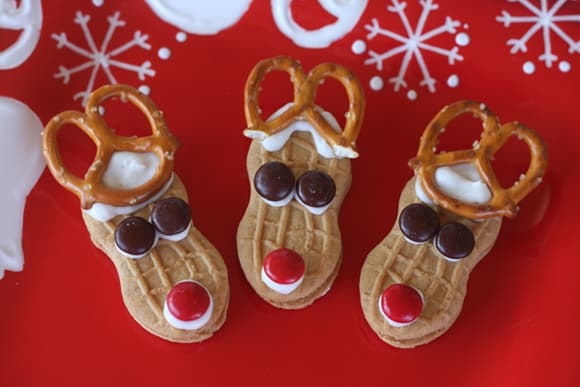 Reindeer Nutter Butter cookies decorated with red noses and pretzel antlers