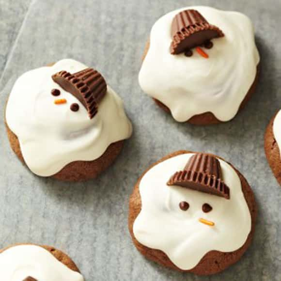 Melted Snowman Cookies wiht Reeses hats and white frosting
