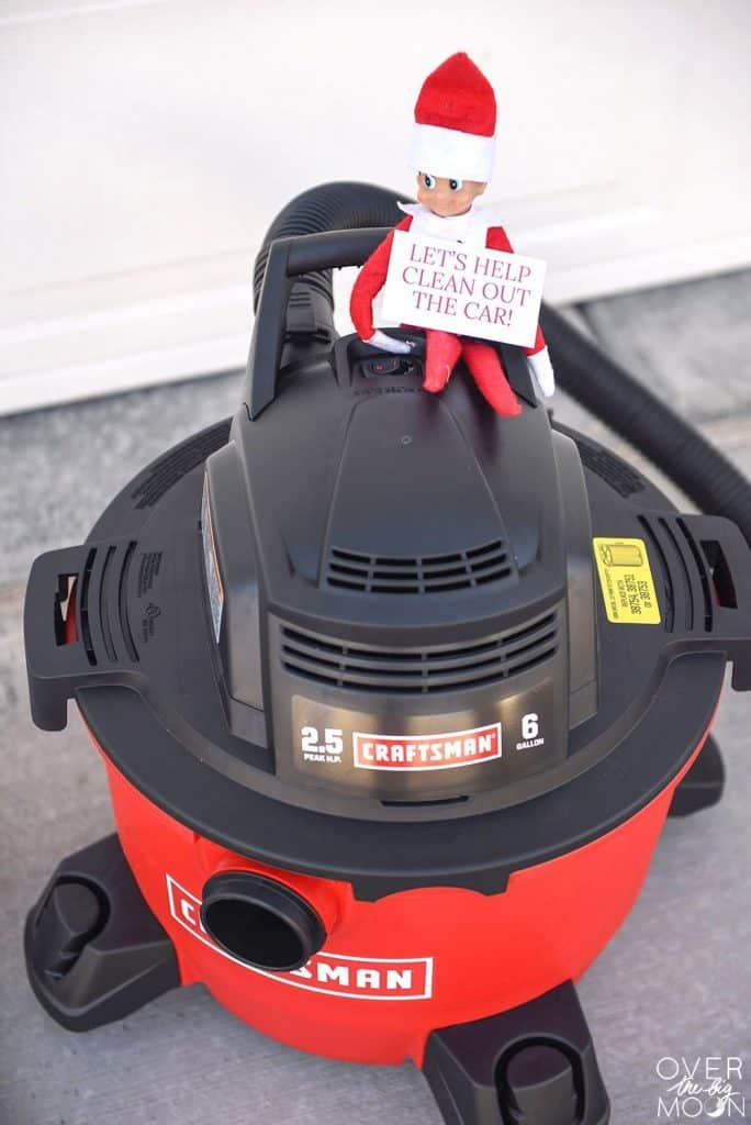 Helpful Elf on the Shelf with a vacuum and a card that reads 'Let's help clean out the car!'