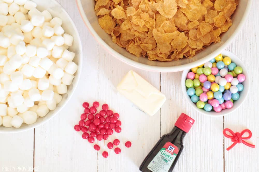 Cornflake Wreath Ingredients - Bowl of cornflakes, bowl of marshmallows, red cinnamon candies, green food coloring, butter and pastel sixlets.