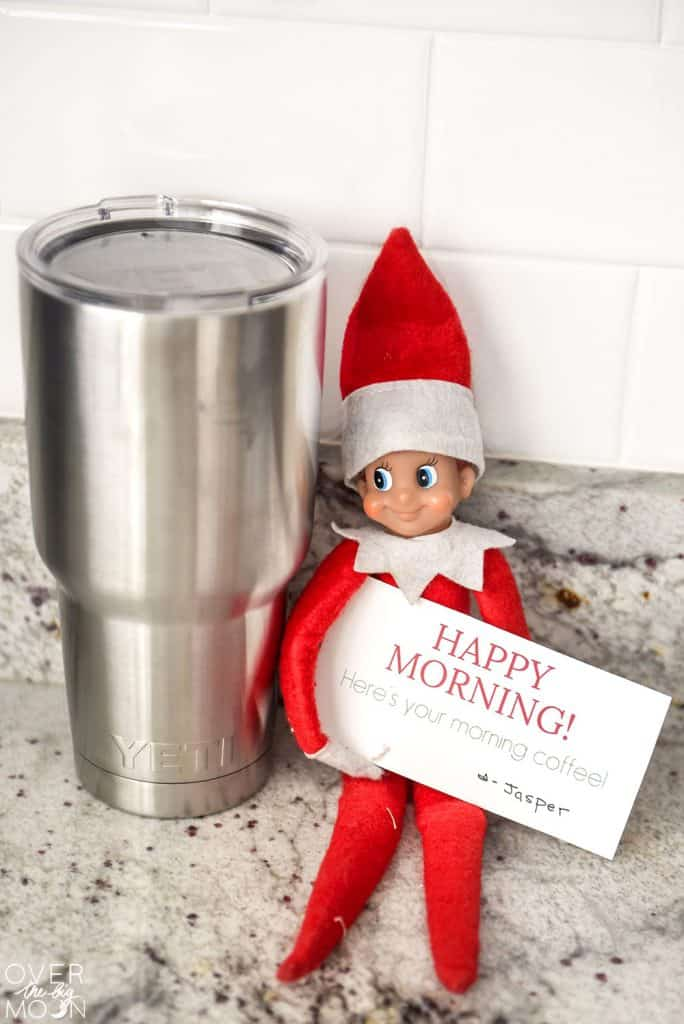 Helpful Elf on the Shelf next to a Yeti tumbler with a card that says 'Happy Morning, here's your coffee'