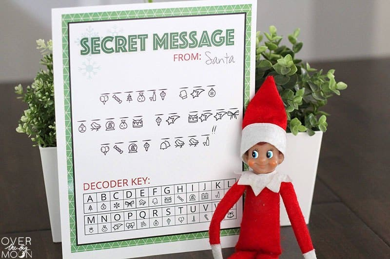 Secret Message from Santa with decoder key on white paper with a green border and Elf on the Shelf next to it.