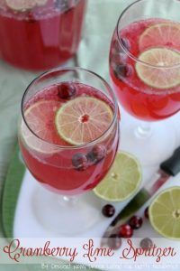 Beautiful red and green cranberry drink garnished with fresh limes