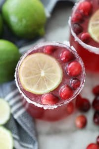 cranberry punch in a sugared glass with a lime slice and fresh cranberries