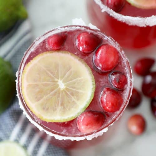 cranberry punch in a sugared glass surrounded by a tea towel, limes and cranberries