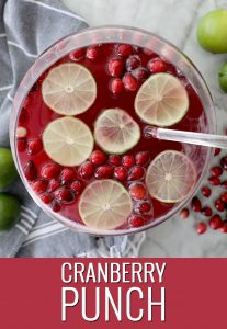 punch bowl of cranberry punch with fresh lime and cranberry garnishes on a marble counter