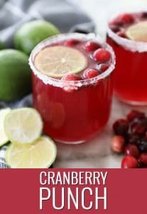 a glass of cranberry punch on a marble counter by fresh limes and cranberries
