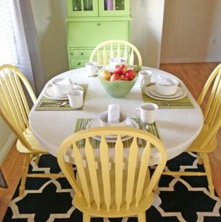 Refinished white table with a tile table top, with yellow dining chairs.