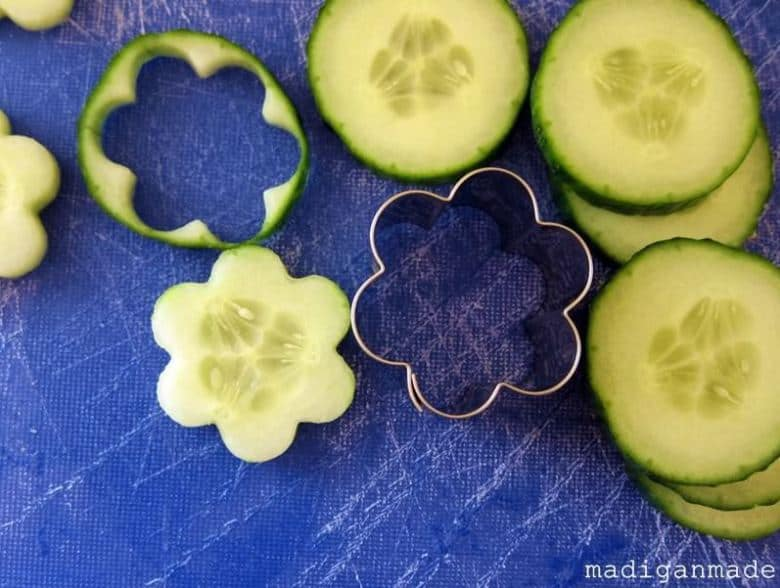 Cucumbers cut into flower shapes with a cookie cutter on a blue cutting board, from Rosyscription.com