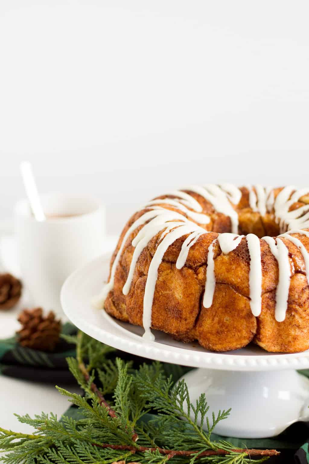 cinnamon monkey bread with white frosting drizzle on a white cake plate