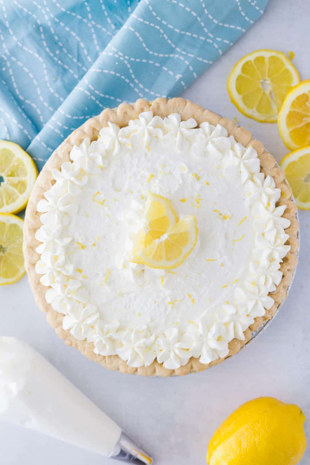 birds eye view of a lemon sour cream pie next to some sliced lemons and a whipped cream piper