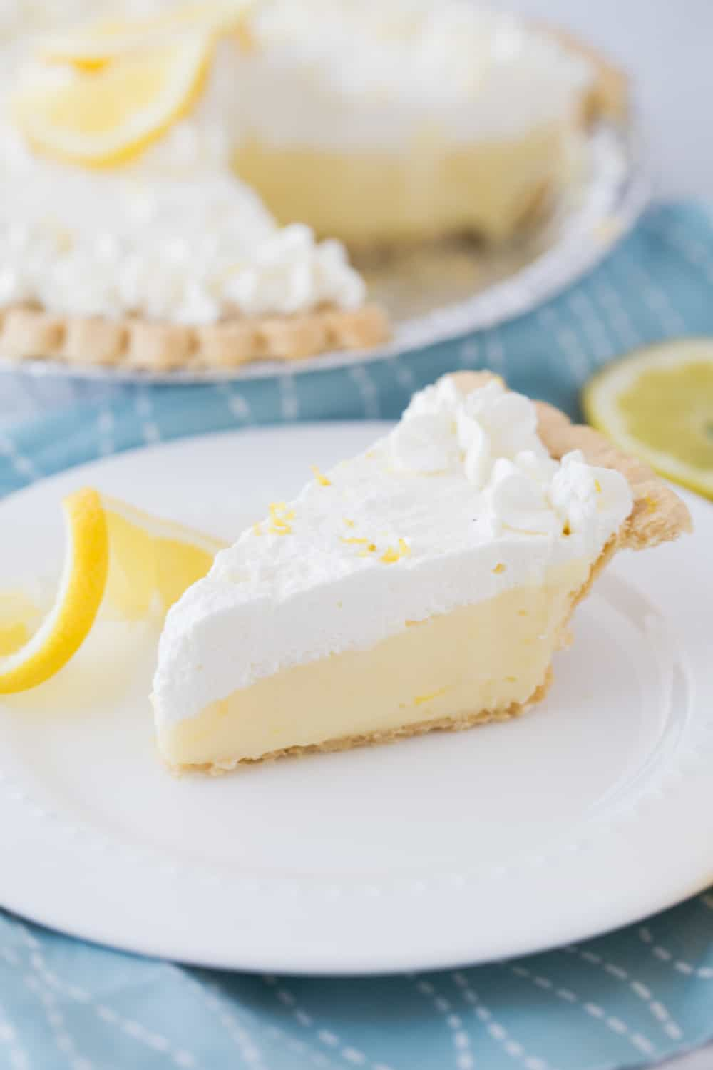 slice of lemon sour cream pie on a white plate on a blue cloth with the full pie in the background