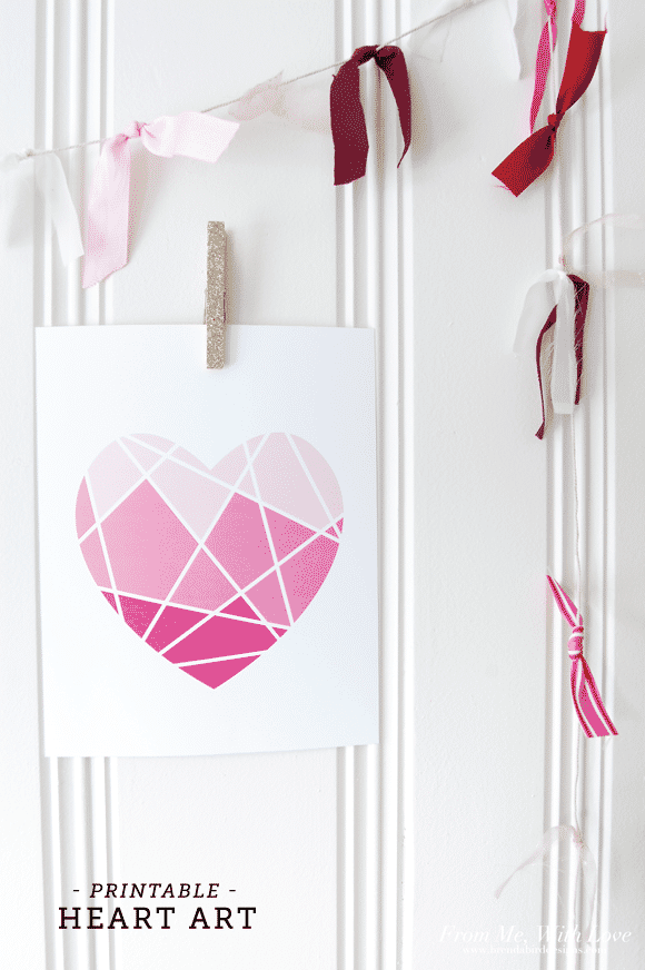 Geometric heart with light pink sections on top, medium pink in the middle and dark pink at the bottom, hung up on a white wall with a clothes pin.