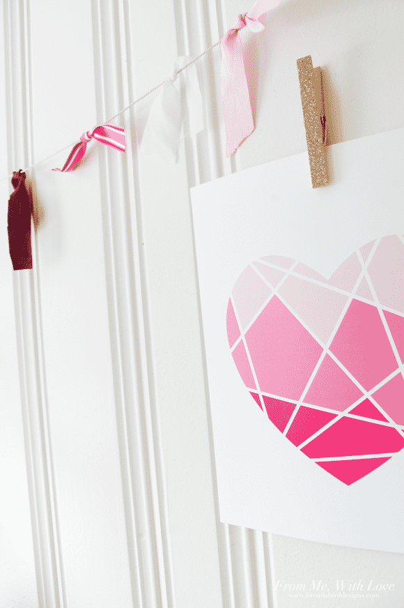 Geometric heart with light pink sections on top, medium pink in the middle and dark pink at the bottom, hung up on a white wall with a clothes pin and a Valentine's Day garland.