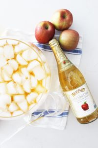 a punch bowl of apple cider with ice next to three apples and a bottle of cider