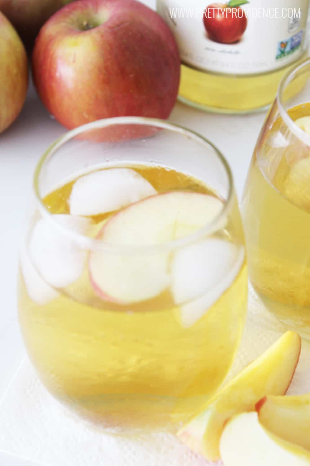 stemless wine glass with ice and sparkling cider, apples and bottom of bottle in background