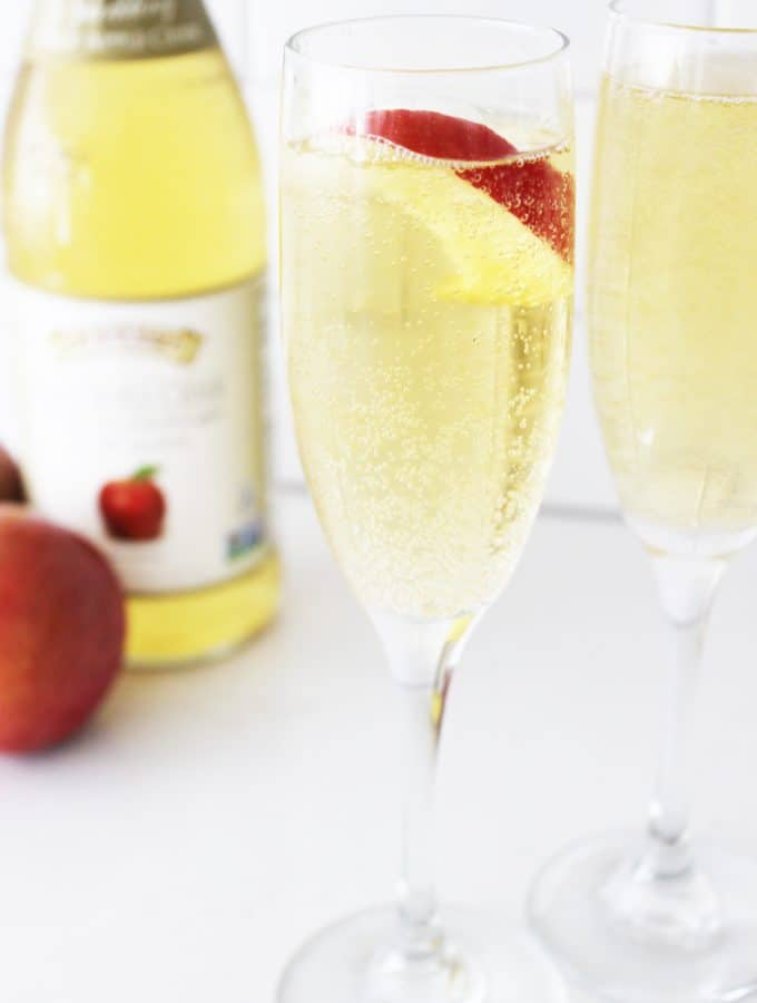 two wine glasses of sparkling apple cider with a bottle and an apple in the background