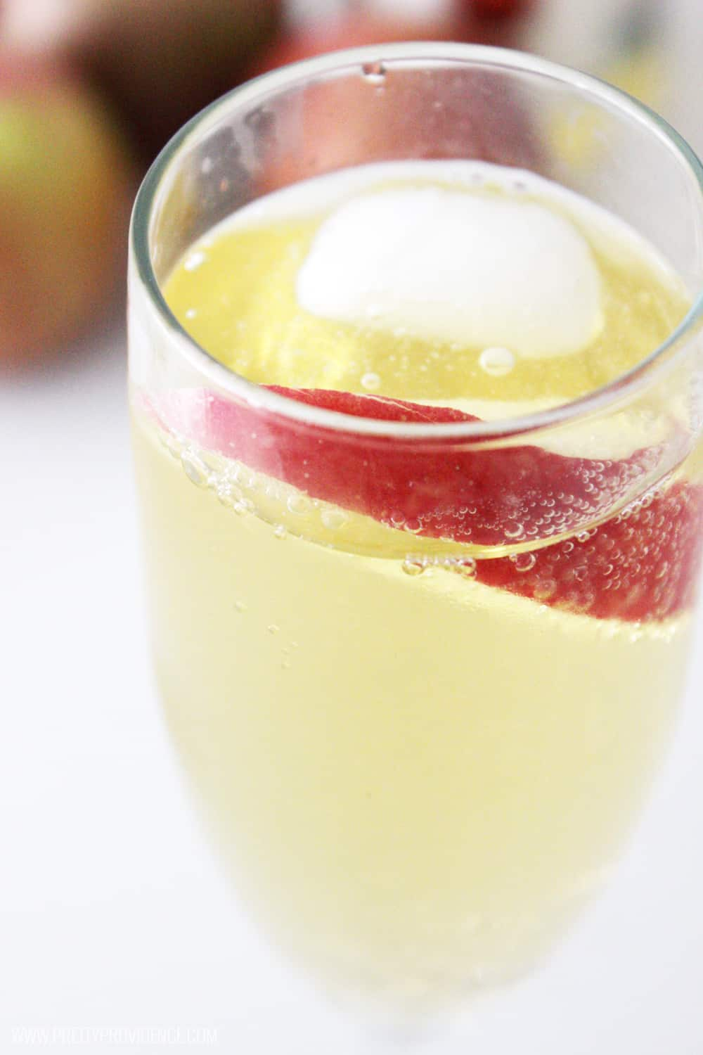 close up view of a glass of sparkling apple cider with apple slice to garnish