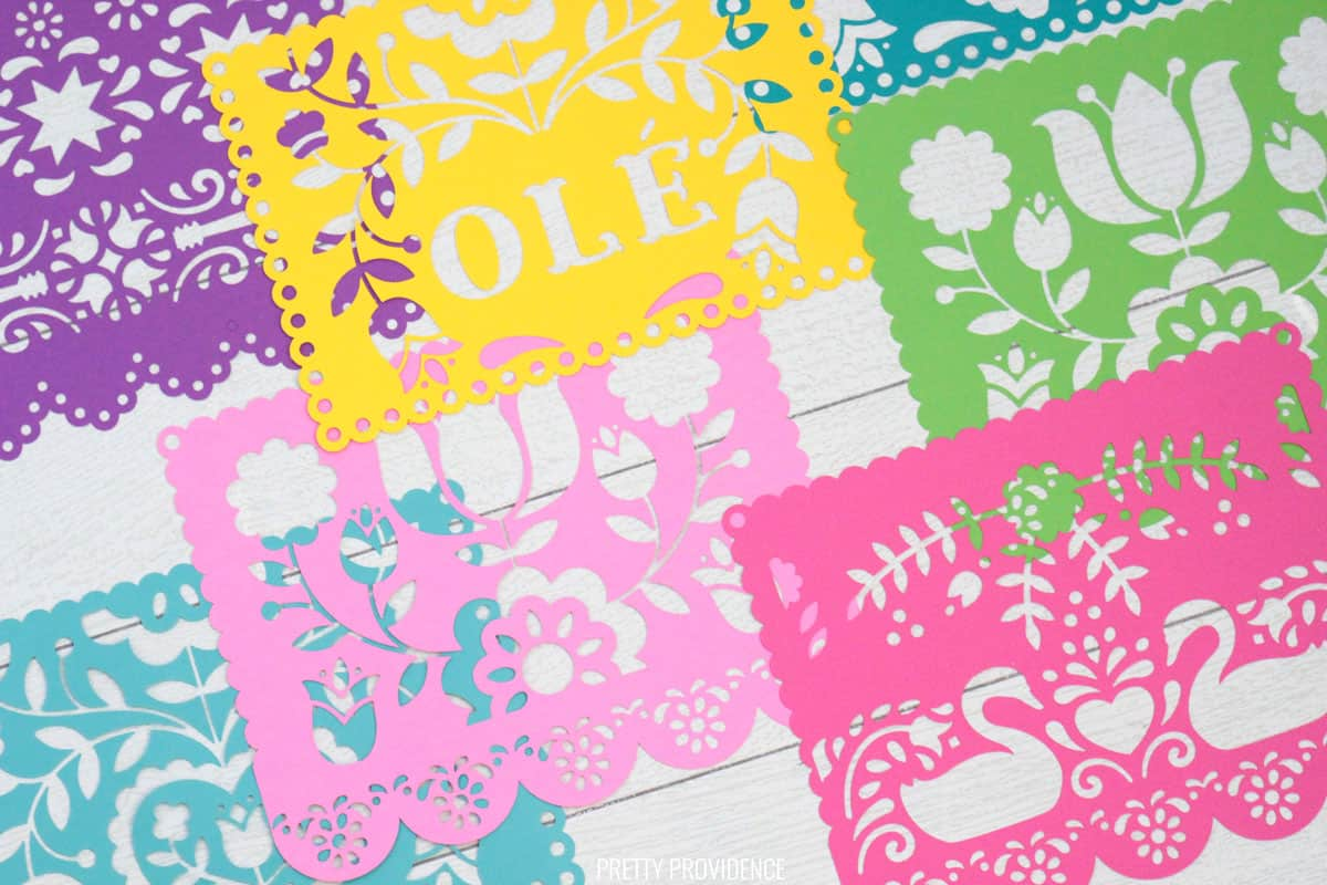 Papel Picado banner sheets made from colorful card stock with Cricut on a white shiplap surface