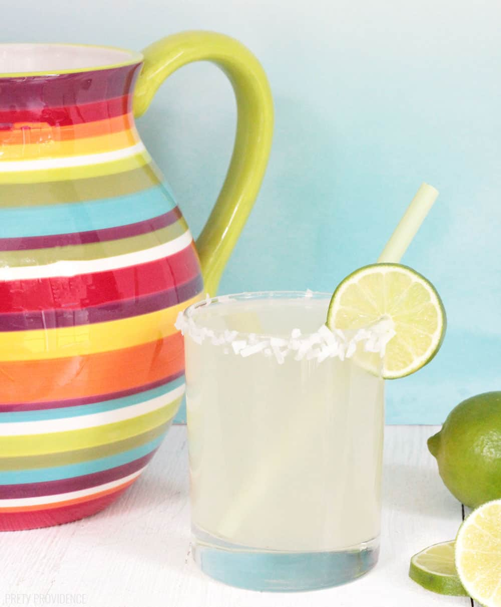 Limeade in a glass with coconut shavings on the rim. A colorful pitcher is in the background.