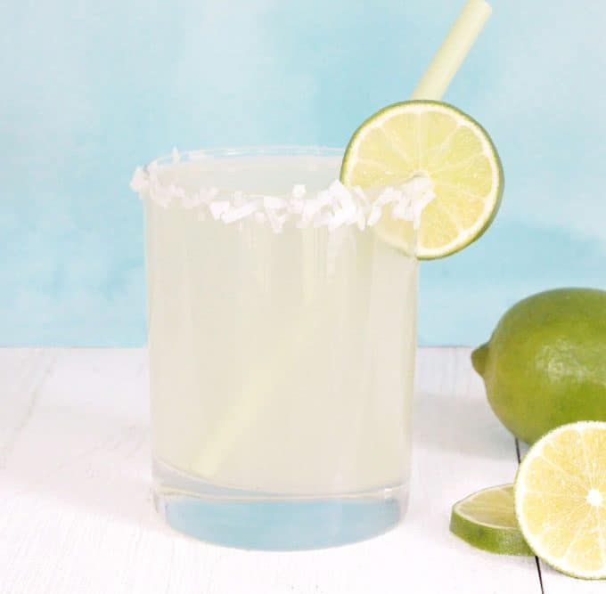 Coconut Limeade in a glass with shredded coconut and a lime slice on the rim, and sliced limes on the side.