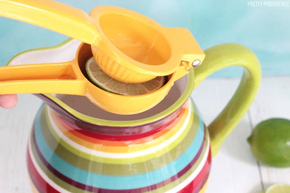 Citrus squeezer with a lime in it, being squeezed over a colorful pitcher.