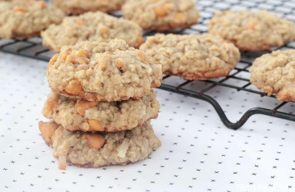Oatmeal Scotchies cookies, three oatmeal scotchies cookies stacked on top of each other with a cooling rack in the background.