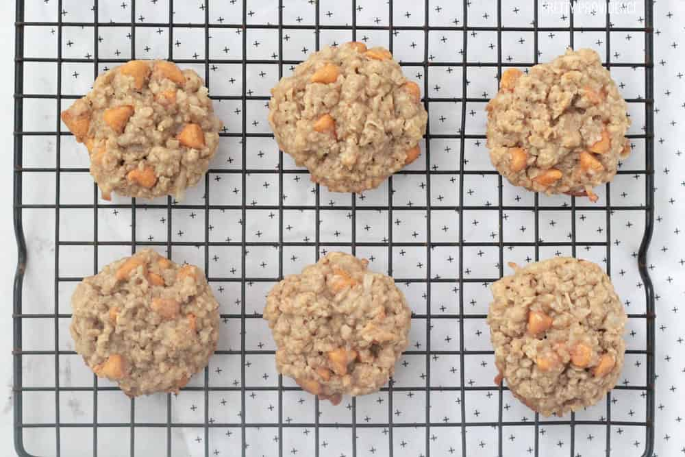 Oatmeal scotchies cookies with butterscotch chips on a cooling rack.