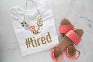 white t-shirt with '#tired' written on it in gold iron-on with sandals and a necklace