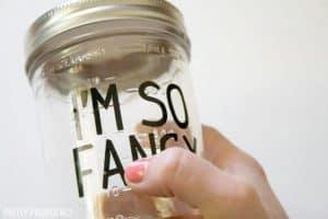 Rubbing black vinyl letters 'I'm So Fancy' onto mason jar